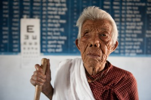 An elderly lady from Nepal who is blind stands in front of an eye chart. She is holding a walking stick.