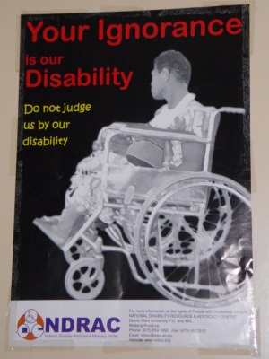 "Picture of an advocacy poster produced by the National Disability Resource and Advocacy Centre, Papua New Guinea. The poster shows a man sitting in a wheelchair in profile. The poster reads ""Your ignorance is our disability; Do not judge us by our disability""."