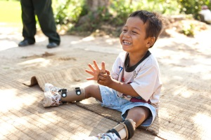 Picture of a smiling young boy from Cambodia sitting outside on a mat. He is wearing braces on both of his legs.