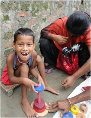Picture of a girl from Bangladesh sitting on a stool, putting wooden shapes on a peg. The CBR worker is squatting beside her.