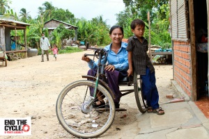 Sieng Sok Chann sits in her hand driven tricycle wheelchair outside her house with a large smile. Her young son leans against her shyly. There is a ramp leading to the doorway. In the background across the road are several more houses surrounded by trees, and a villager and small child walk are walking together along the road.