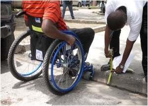Picture of a man in a wheelchair stopped at a curb. Another man is bending over measuring the curb height with a tape measure.