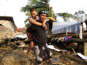Picture of a woman from the Philippines supported on her father's back. She has cerebral palsy. There is destroyed houses and debris in the background.