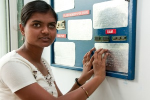 Picture of a young woman from India with a vision impairment reading Braille plates attached to the wall.  (The plates contain information about computer parts.)