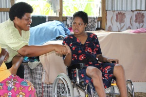 Picture of a girl from Fiji seated in a wheelchair, shaking hands with a woman representative from the Fiji Disabled Persons Federation.