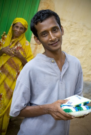 Picture of a man from India holding a packet of milk that is for sale. His mother is in the background looking on.