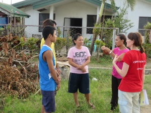 Picture of three students standing in front of a house that has been damaged by Typhoon Haiyan. They are talking to a visitor using sign language and an interpreter. There is a tree on the ground next to the students.