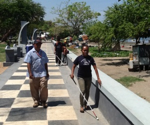 Picture of a woman in Timor Leste who is blind walking along a footpath at the waterfront with a mobility cane. A male orientation and mobility trainer is walking alongside her.